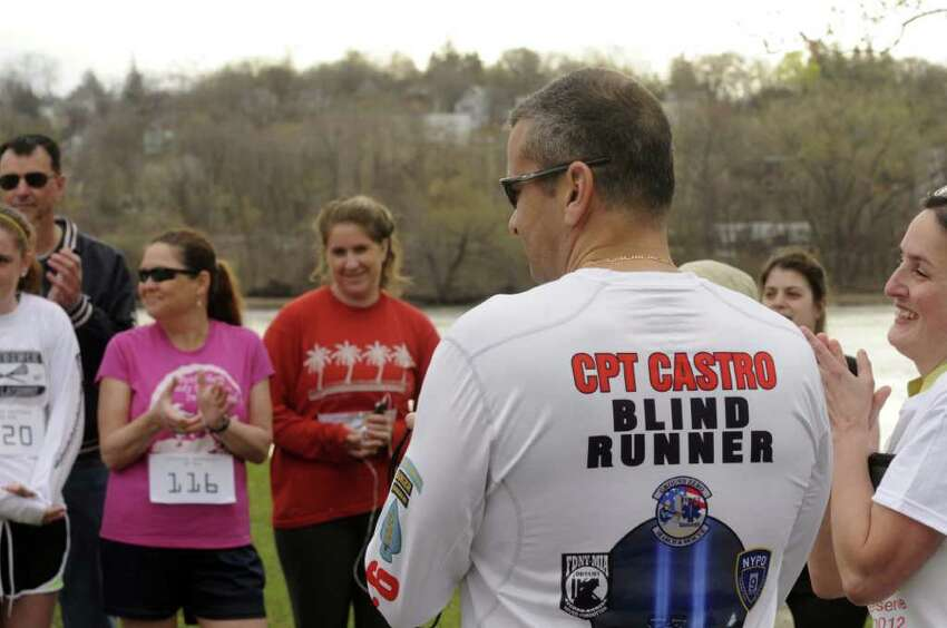 Decorated and active duty blind Army Captain Ivan Castro, right, speaks with other runners prior to the start of a 5K race to raise awareness on military veteran's need at the Corning Preserve in Albany N.Y., Saturday March 24, 2012. (Michael P. Farrell/Times Union)