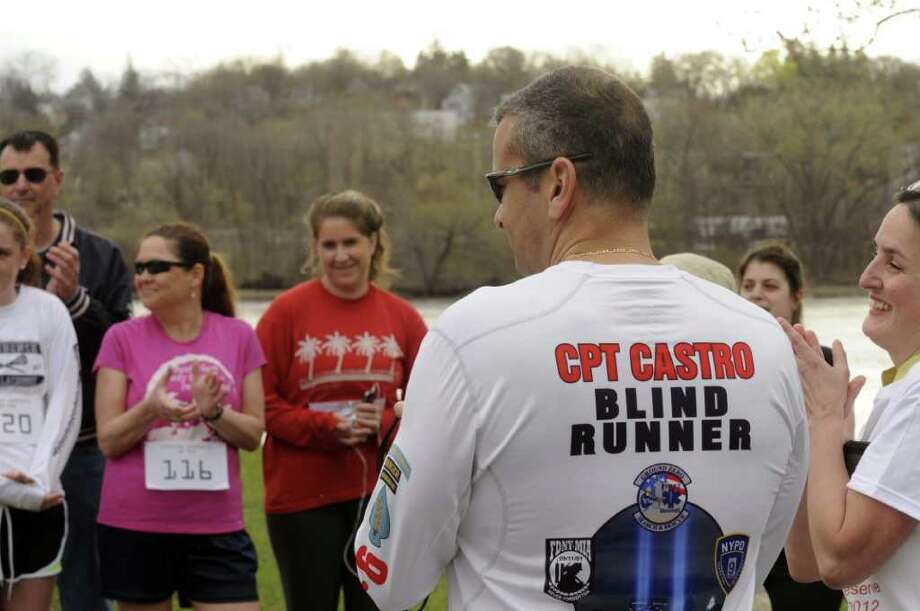 Decorated and active duty blind Army Captain Ivan Castro, right, speaks with other runners prior to the start of a 5K race to raise awareness on military veteran's need at the Corning Preserve in Albany N.Y., Saturday March 24, 2012. (Michael P. Farrell/Times Union) Photo: Michael P. Farrell