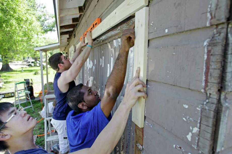 Second Baptist Church volunteers Joey Jurkash, rear, Stanley Ninan, center, and Felix Lincoln, foreground, cooperate to replace trim Saturday on a home on Keystone during the Rebuilding Together Houston project. Photo: Melissa Phillip / © 2012 Houston Chronicle
