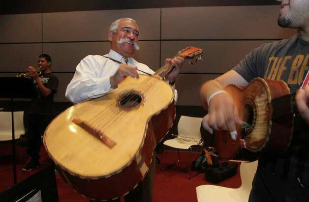 Juan Ortiz (center) smiles Thursday March 22, 2012 while playing music in the mariachi class he teaches at Palo Alto College. Ortiz has won two Grammys but has kept pretty quiet about it. Playing on the right is student Carlton Galvez. John Davenport/San Antonio Express-News Photo: JOHN DAVENPORT, SAN ANTONIO EXPRESS-NEWS / SAN ANTONIO EXPRESS-NEWS (Photo can be sold to the public)