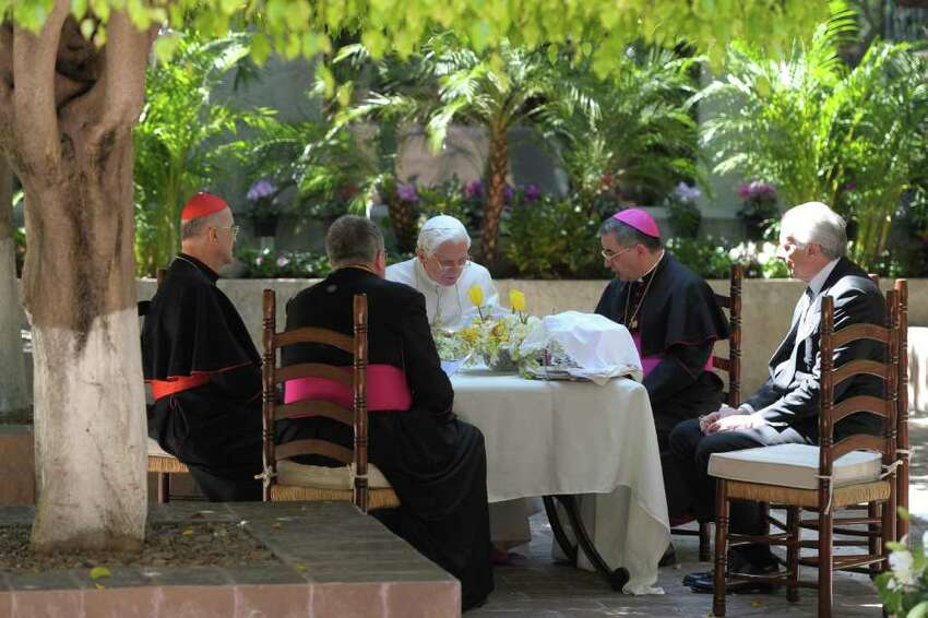 In this picture made available by the Vatican newspaper Osservatore Romano, Pope Benedict XVI, center, sits with prelates in the yard of Colegio de Miraflores in Leon, Mexico, Saturday March 24, 2012. Benedict arrived in Mexico Friday afternoon, a decade after the late Pope John Paul II's last visit, and will travel to Cuba on Monday.