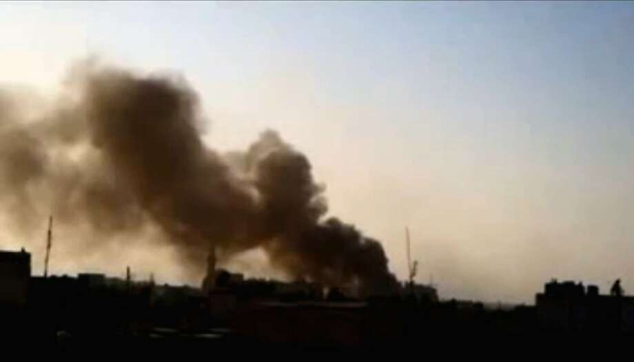 This image made from amateur video and released by Shaam News Network Saturday, March 24, 2012, purports to show smoke rising after rockets fell in the Khaldiyeh area of Homs, Syria. (AP Photo/Shaam News Network via AP video) Photo: Anonymous, Associated Press