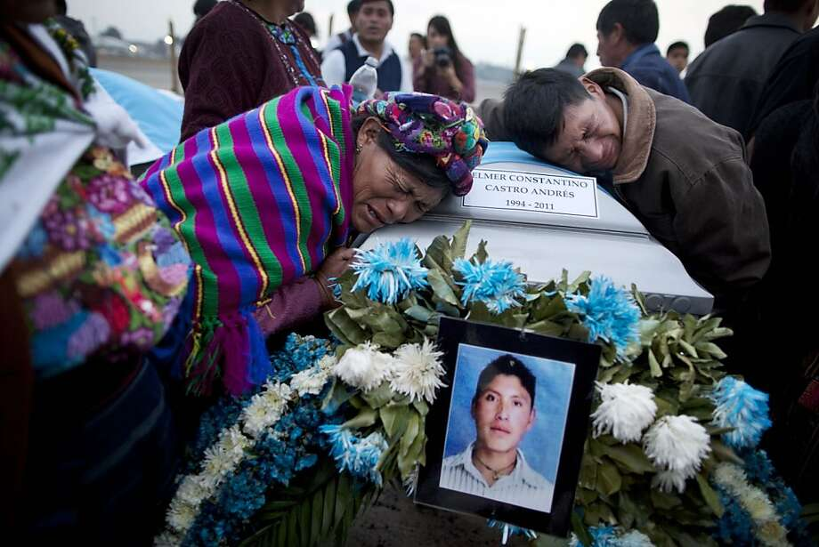 Natalia Andres Lopez,  left, and another relative, mourn over the coffin containing the body of her cousin, at an Air Force base in Guatemala City , Wednesday, March 21, 2012. The remains of 11 Guatemalan citizens were repatriated from Mexico Wednesday, part of 193 bodies found in the northern Mexico Tamaulipas state in 26 mass graves in April 2011. Mexican authorities believe the dead were mostly migrants kidnapped from buses and killed by the Zetas drug cartel.(AP Photo/Rodrigo Abd) Photo: Rodrigo Abd, Associated Press