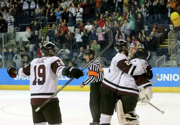 Kelly Zajac, left, and #22 Mat Bodie, center, celebrate with goalie #1 Troy Grosenick after the team defeated UMASS Lowell 4-2, during NCAA Men's Ice Hockey Bridgeport Regional action at the Webster Bank Arena in Bridgeport, Conn. on Saturday March 24, 2012. Photo: Christian Abraham / Connecticut Post