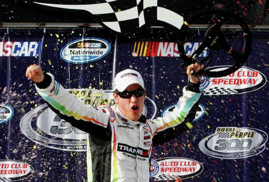 Joey Logano celebrates after winning Saturday's NASCAR Nationwide Series race at Fontana, Calif. Photo: Lesley Ann Miller / AP2012