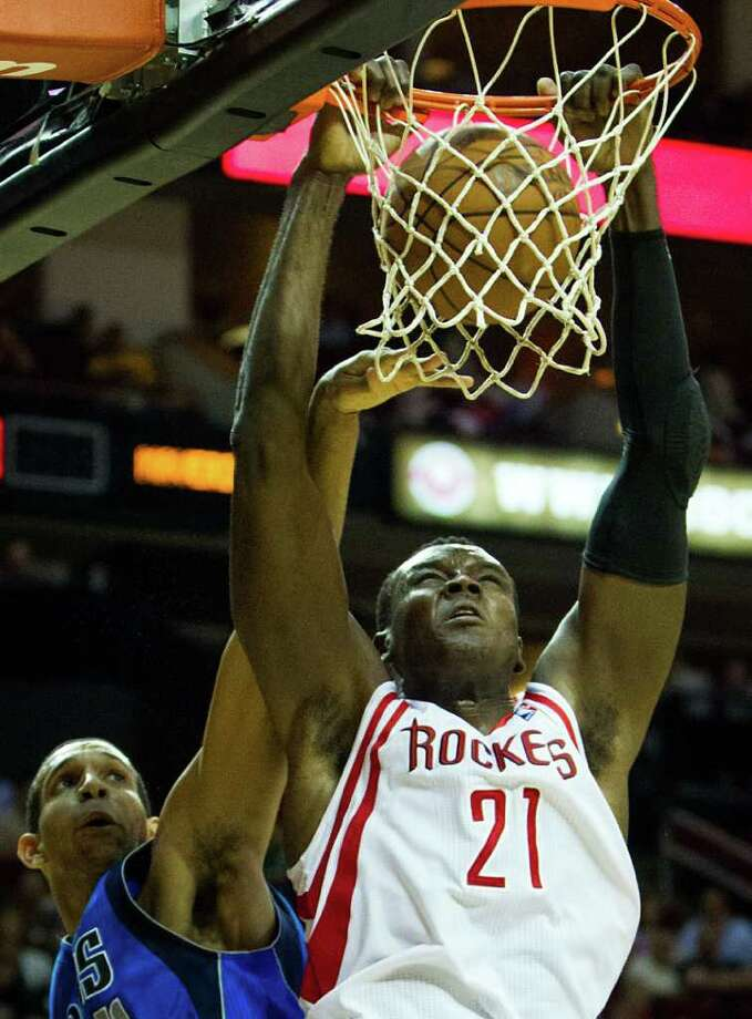 Houston Rockets center Samuel Dalembert (21) dunks over Dallas Mavericks power forward Brandan Wright (34) during the first half of an NBA basketball game at Toyota Center on Saturday, March 24, 2012, in Houston. Photo: Smiley N. Pool, Houston Chronicle / © 2012  Houston Chronicle