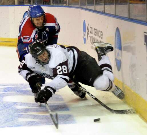 Union's #28 Shawn Stuart takes a spill in front of UMASS Lowell's #12 Josh Holmstrom, during NCAA Men's Ice Hockey Bridgeport Regional action at the Webster Bank Arena in Bridgeport, Conn. on Saturday March 24, 2012. Photo: Christian Abraham / Connecticut Post