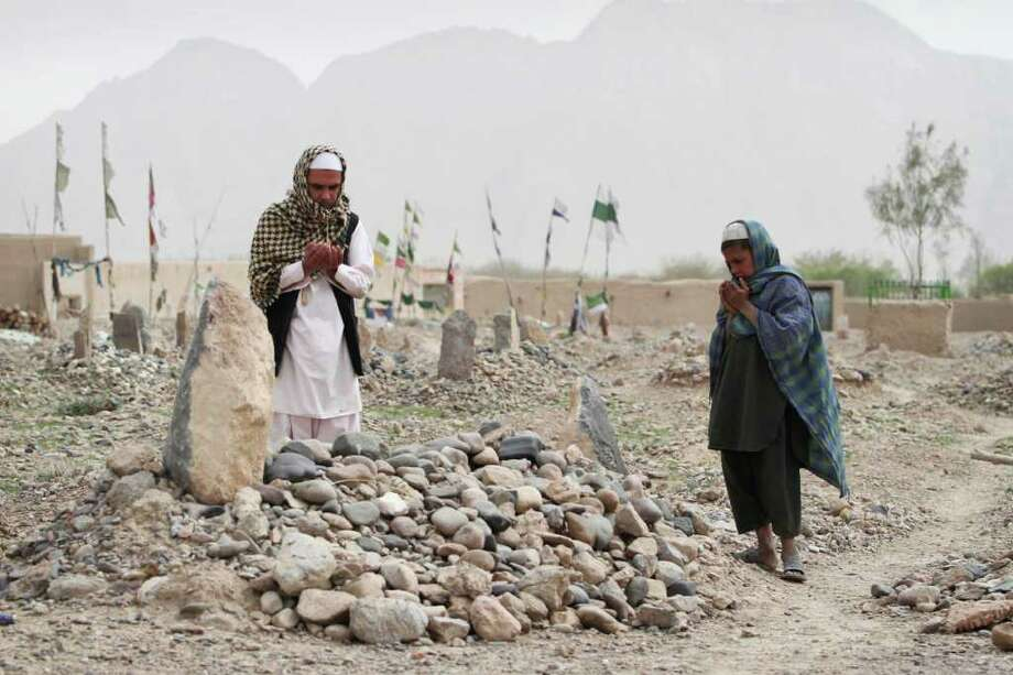 Afghan villagers pray over the grave of one of the sixteen victims killed in a shooting rampage in the Panjwai district of Kandahar province south of Kabul, Afghanistan, Saturday, March 24, 2012. Mohammad Wazir has trouble even drinking water now, because it reminds him of the last time he saw his seven-year-old daughter. He had asked his wife for a drink but his daughter insisted on fetching it. Now his daughter Masooma is dead, killed along with 10 other members of his family in a shooting rampage attributed to a U.S. soldier. The soldier faces the death penalty but Wazir and his neighbors say they feel irreparably broken. (AP Photo/Allauddin Khan) Photo: Allauddin Khan  / AP