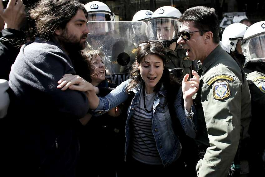 Protestors scuffle with riot police during Greek Independence Day in Athens on March 24, 2012. Authorities in Greece are implementing massive security measures amidst fears that anti-austerity protests could disrupt national parades over the weekend. TOPSHOTS AFP PHOTO / Angelos Tzortzinis (Photo credit should read ANGELOS TZORTZINIS/AFP/Getty Images)