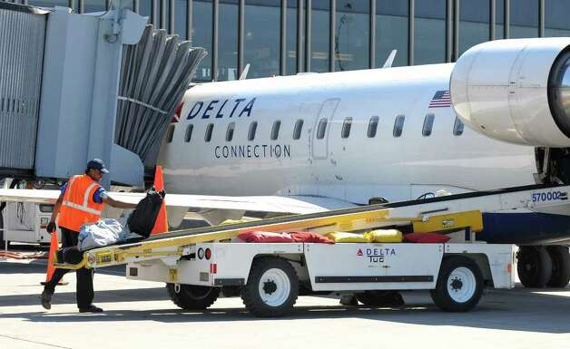 Baggage is loaded onto a Delta Connection flight to JFK airport in New York City,  before it took off from the Albany International Airport on Wednesday March 21, 2012 in Colonie, N.Y.  (Philip Kamrass / Times Union ) Photo: Philip Kamrass / 00016923A
