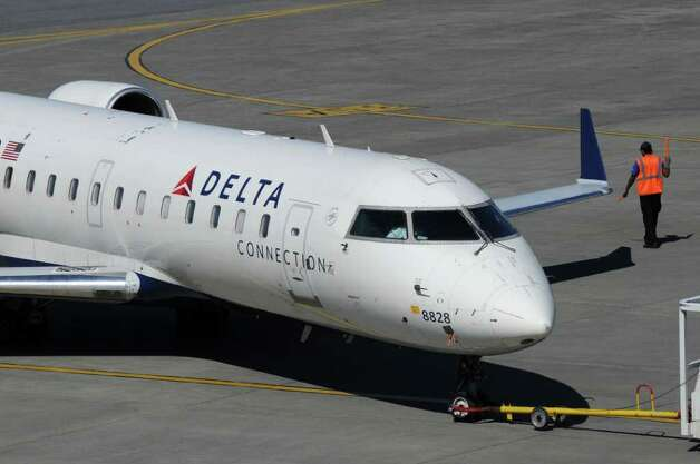 Ground crew guide a Delta Connection flight away from the Albany International Airport terminal, before taking off for JFK airport in New York City,   on Wednesday March 21, 2012 in Colonie, N.Y.  (Philip Kamrass / Times Union ) Photo: Philip Kamrass / 00016923A