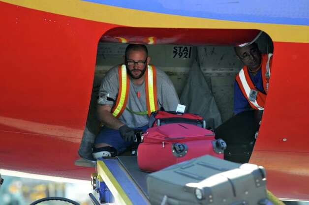 Baggage handlers load a Southwest Airlines jet bound for Las Vegas, before it departed from the Albany International Airport on Wednesday March 21, 2012 in Colonie, N.Y.  (Philip Kamrass / Times Union ) Photo: Philip Kamrass / 00016923A