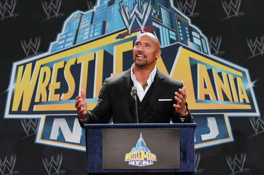 """ADVANCE FOR WEEKEND EDITIONS, MARCH 24-25 - FILE - In this Feb. 16, 2012 file photo, World Wrestling Entertainment personality Dwayne """"The Rock"""" Johnson speaks at a news conference in East Rutherford, N.J.  The Rock returns to the WWE for his first WrestleMania match since 2004 when he headlines the April 1 card against John Cena.  (AP Photo/StarPix, Dave Allocca) Photo: Dave Allocca"""