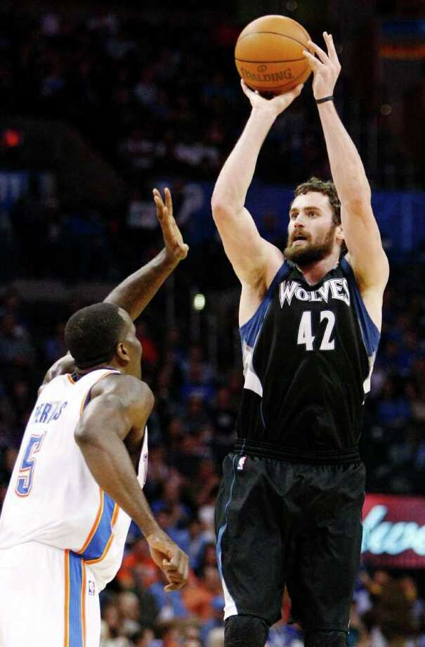 Minnesota Timberwolves center Kevin Love (42) shoots the ball in front of Oklahoma City Thunder's Kendrick Perkins (5) during the second quarter of a NBA basketball game in Oklahoma City, Friday, March 23, 2012. (AP Photo/Alonzo Adams) Photo: Alonzo Adams