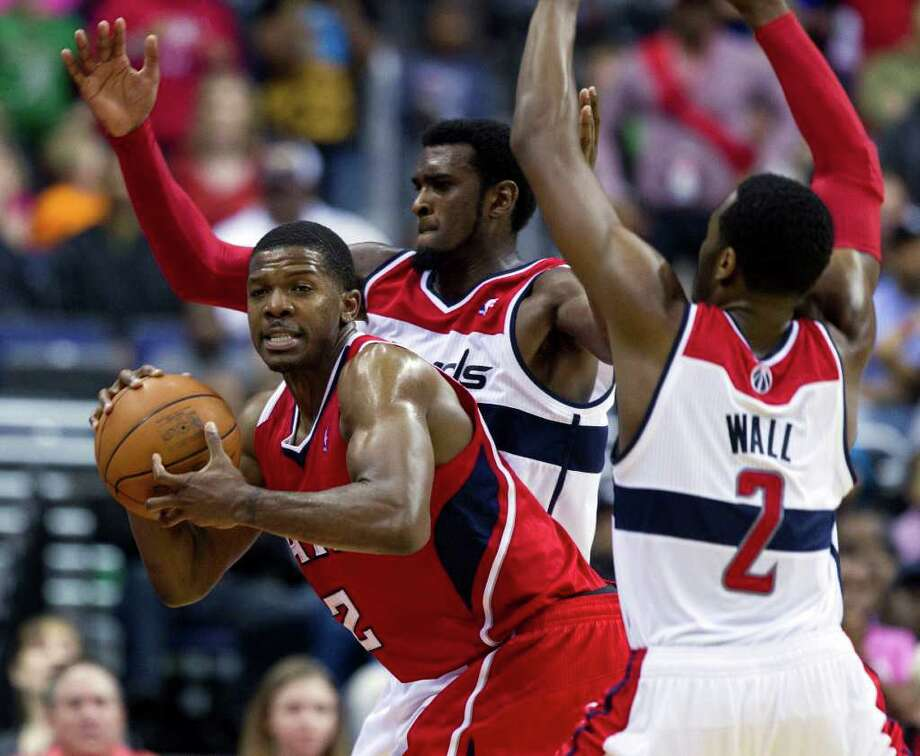 Atlanta Hawks' Joe Johnson, left, tries to keep the ball away from Washington Wizards defenders Chris Singleton, center, and John Wall (2) during the closing seconds of the second half of an NBA basketball game on Saturday, March 24, 2012 in Washington. The Hawks defeated the Wizards 95-92.  (AP Photo/Evan Vucci) Photo: Evan Vucci / AP