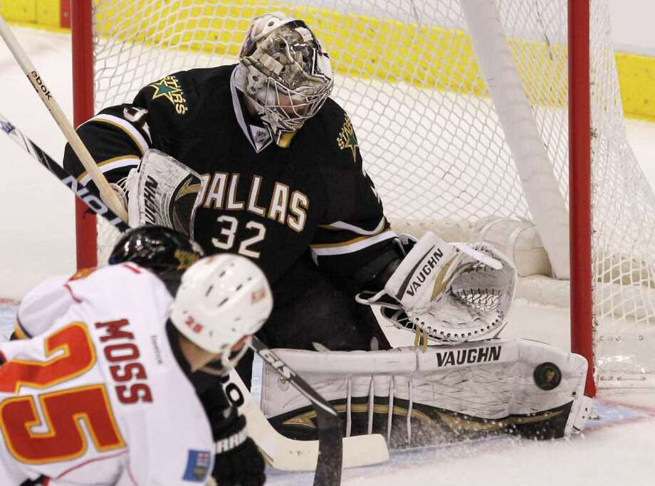 Dallas Stars goalie Kari Lehtonen (32) makes a save against Calgary Flames right wing David Moss (25) during the first period of an NHL hockey game in Dallas, Saturday, March 24, 2012.  Lehtonen had 35 saves in the 4-1 win. (AP Photo/LM Otero) Photo: LM Otero