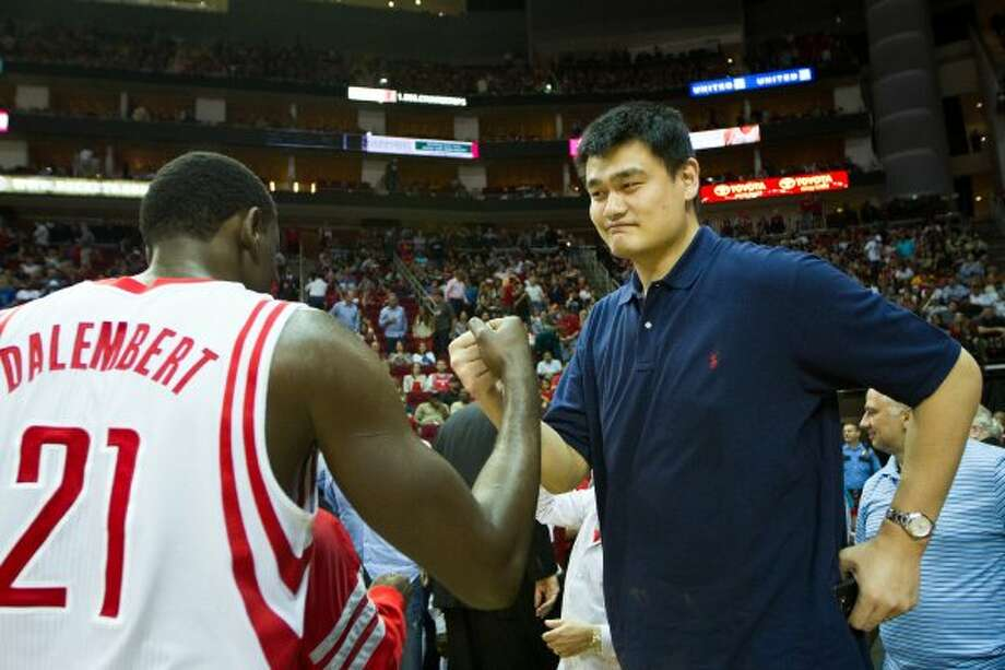 Rockets center Samuel Dalembert (21) is congratulated by former Rockets center Yao Ming as he leaves the court at the end of the first half. (Smiley N. Pool / Houston Chronicle)