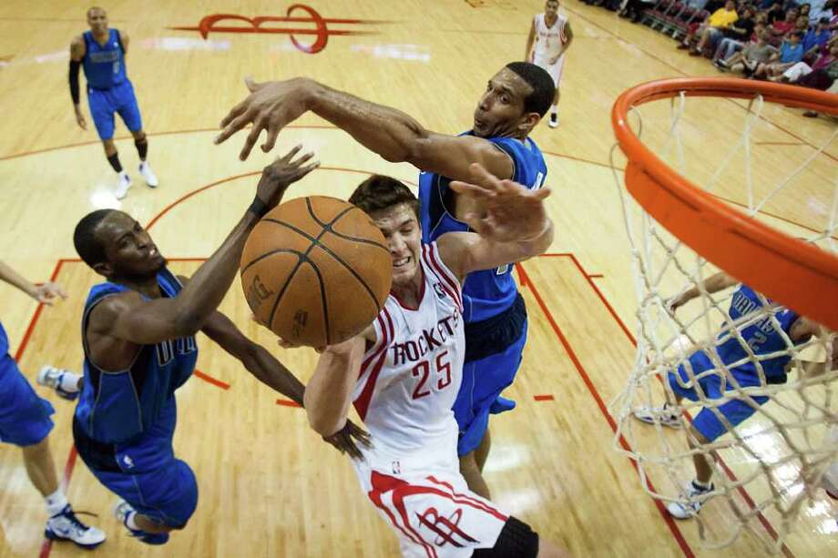 Rockets forward Chandler Parsons drives to the basket between Mavericks guard Roddy Beaubois, left, and forward Brandan Wright during the first half. Parsons finished with 12 points on 5-for-16 shooting. Photo: Smiley N. Pool / © 2012  Houston Chronicle