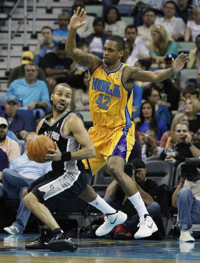 Spurs guard Tony Parker, left, keeps the ball from New Orleans Hornets' Lance Thomas (42) in the first half of an NBA basketball game in New Orleans, Saturday, March 24, 2012. (AP Photo/Bill Haber) (AP)