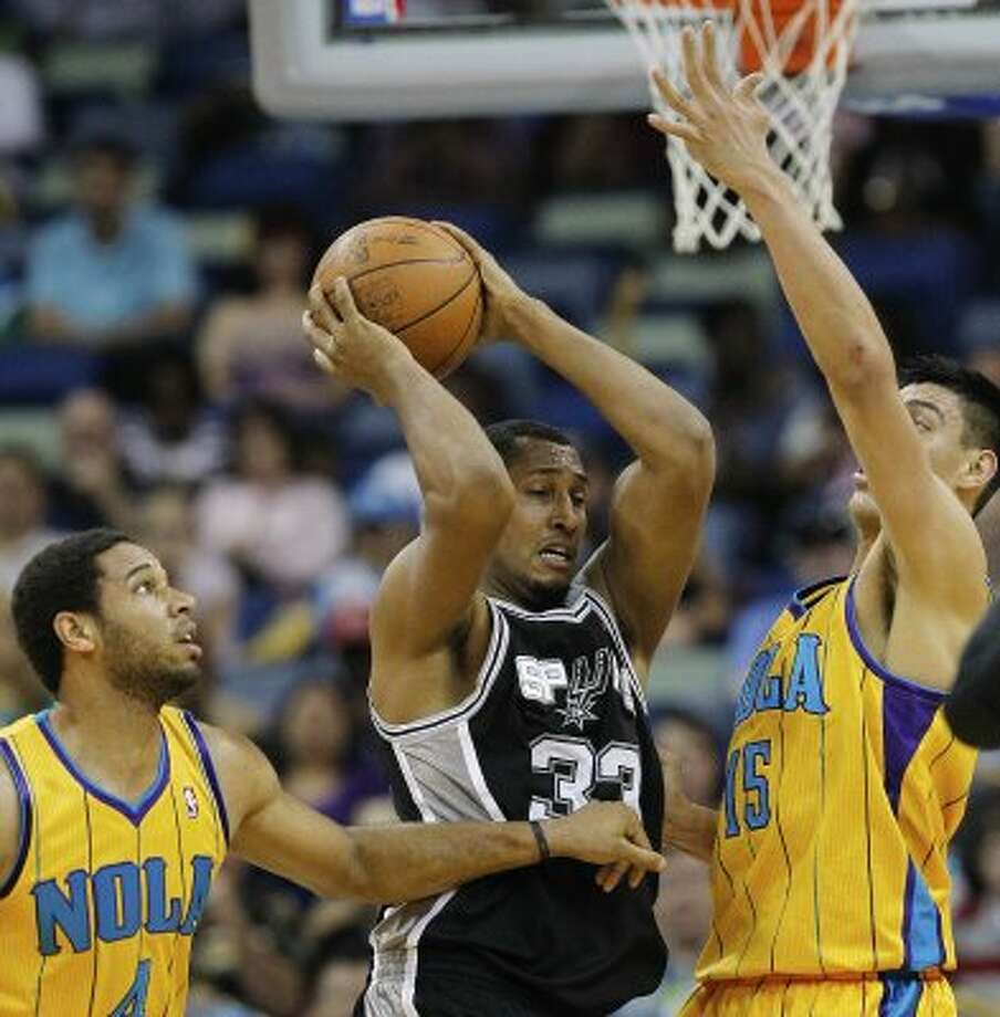New Orleans Hornets guard Xavier Henry (4) and center Gustavo Ayon (15) defend Spurs forward Boris Diaw (33) in the first half of an NBA basketball game in New Orleans, Saturday, March 24, 2012. (AP Photo/Bill Haber) (AP)
