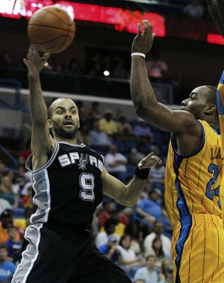 Spurs guard Tony Parker (9) passes around New Orleans Hornets forward Carl Landry (24) in the second half of an NBA basketball game in New Orleans, Saturday, March 24, 2012. The Spurs defeated the Hornets 89-86. (AP Photo/Bill Haber) (AP)