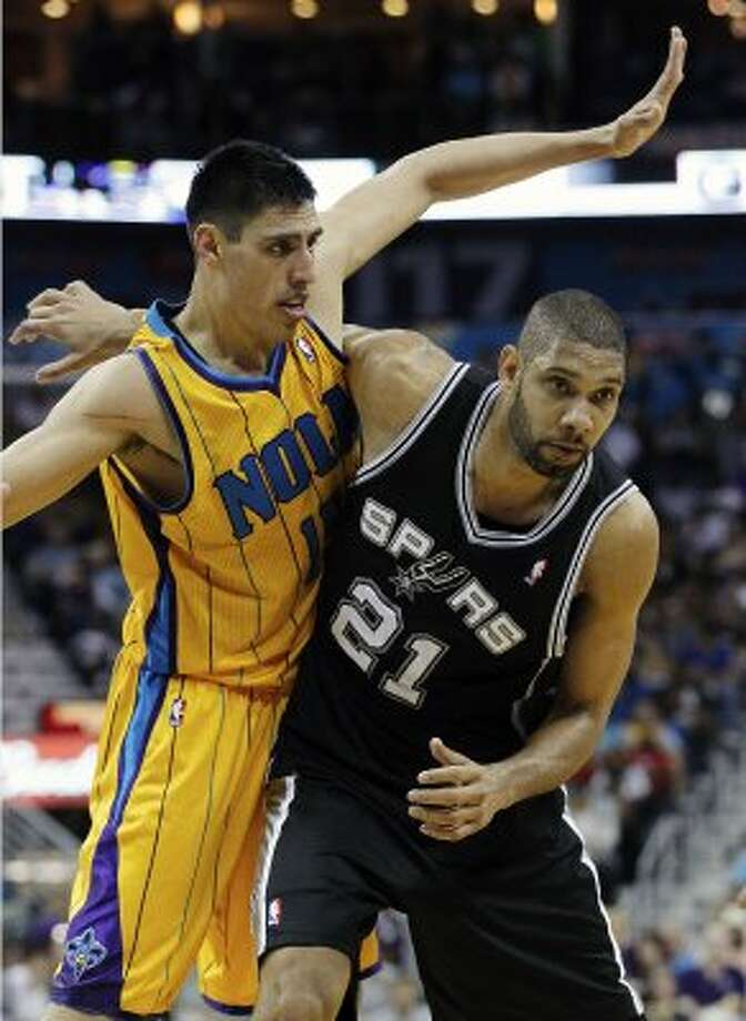 Spurs center Tim Duncan (21) and New Orleans Hornets forward Gustavo Ayon (15)  tangle in the second half of an NBA basketball game in New Orleans, Saturday, March 24, 2012. The Spurs defeated the Hornets 89-86. (AP Photo/Bill Haber) (AP)