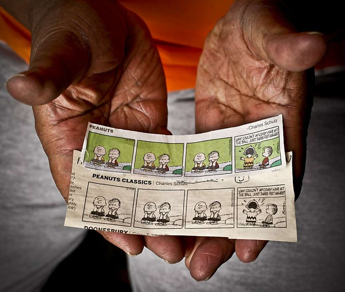 Baseball Hall of Fame Giant Willie McCovey holds two Peanuts comic strip reprints that originally published in 1962 and 1963 that depict Charlie Brown's reaction to the 1962 World Series in his Woodside, Calif., home on Wednesday, Feb. 1, 2012.