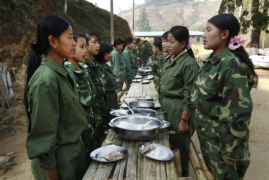 In this Feb. 13, 2012 photo, female recruits of the Kachin Independence Army, one of the country's largest armed ethnic groups, pray before breakfast at a military camp near Laiza, the area controlled by the Kachin in northern Myanmar. The Kachin ethnic minority was promised its freedom in 1948, and is still waiting for the military-backed government to deliver. Meanwhile, the war continues to generate waves of refugees and allegations of atrocities. (AP Photo/Vincent Yu) Photo: Vincent Yu, Associated Press