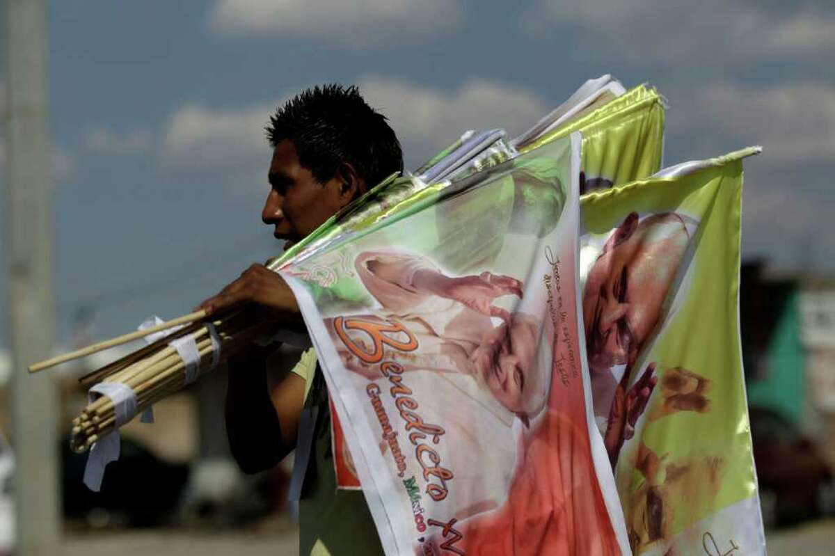 A vendor sells flags with the image of Pope Benedict XVI on a road near the site where the pontiff will give Sunday Mass at the Bicentennial Park near Silao, Mexico, Saturday March 24, 2012.