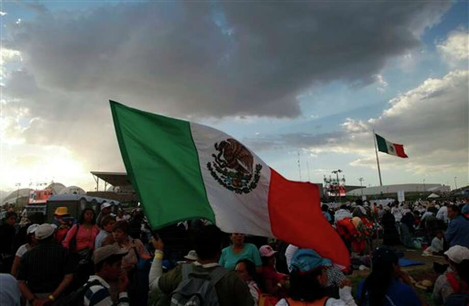 Pilgrims holding a Mexican flag at the site where Pope Benedict will give Sunday Mass at the Bicentennial Park near Silao, Mexico, Saturday March 24, 2012.(AP Photo/Dario Lopez-Mills) Photo: Associated Press