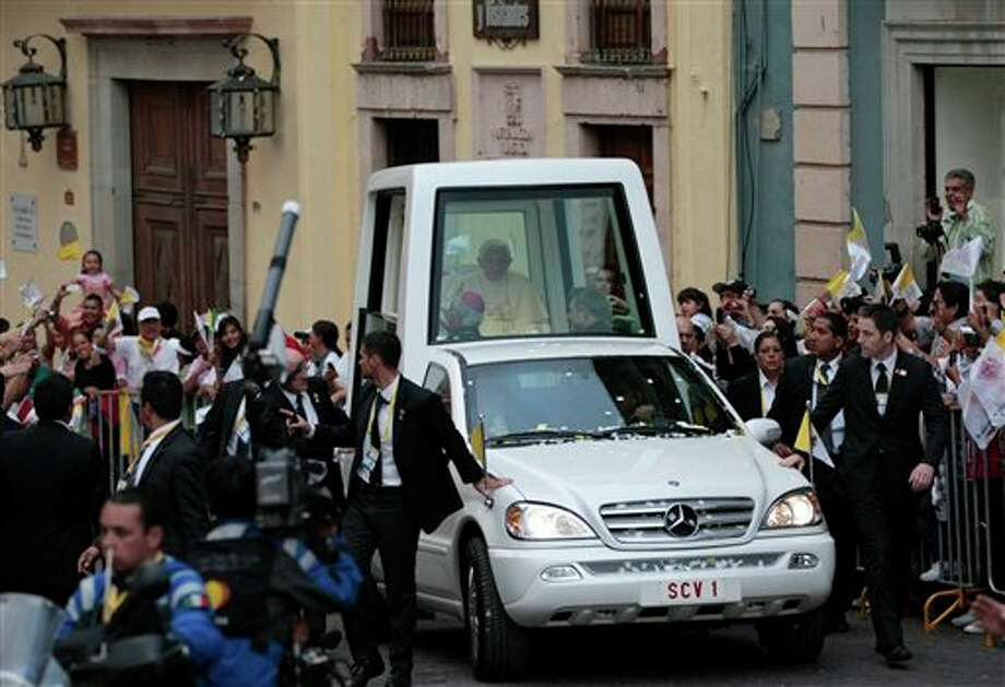 Pope Benedict XVI is cheered by faithful as he arrives aboard the popemobile in Guanajuato, Mexico, Saturday, March 24, 2012.  Benedict arrived in Mexico Friday afternoon, a decade after the late Pope John Paul II's last visit. Benedict's weeklong trip to Mexico and Cuba is his first to both countries. (AP Photo/Gregorio Borgia) Photo: Associated Press