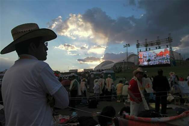 Pilgrims watch live coverage of Pope Benedict XVI's visit to Mexico on a giant TV screen at the site where the pontiff will give Sunday Mass at the Bicentennial Park near Silao, Mexico, Saturday March 24, 2012. Photo: Associated Press