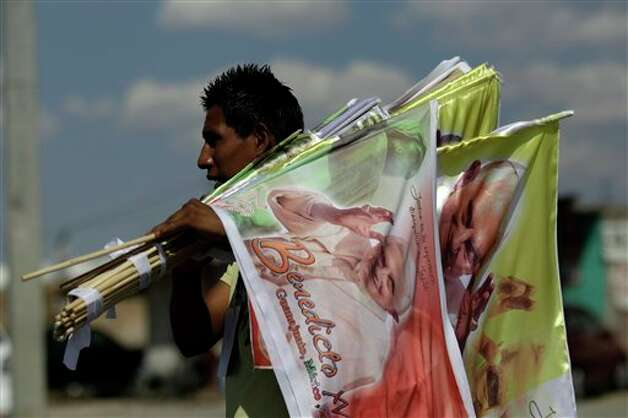 A vendor sells flags with the image of Pope Benedict XVI on a road near the site where the pontiff will give Sunday Mass at the Bicentennial Park near Silao, Mexico, Saturday March 24, 2012.  Photo: Associated Press
