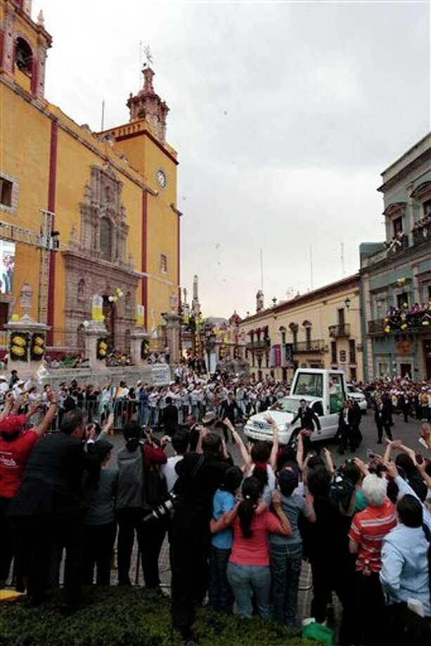 Pope Benedict XVI is cheered by faithful as he arrives in his popemobile in the Plaza de la Paz or Peace Plaza in Guanajuato, Mexico, Saturday March 24, 2012.  At the entrance to Guanajuato, Benedict received the keys to the city. The pope reserved his only public remarks Saturday for a gathering of about 4,000 children and their parents massed in the plaza. (AP Photo/Gregorio Borgia) Photo: Associated Press