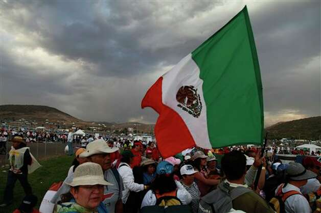 Pilgrims carry a Mexican flag as they arrive to the site where Pope Benedict XVI will give Sunday Mass at the Bicentennial Park near Silao, Mexico, Saturday March 24, 2012.  Photo: Associated Press