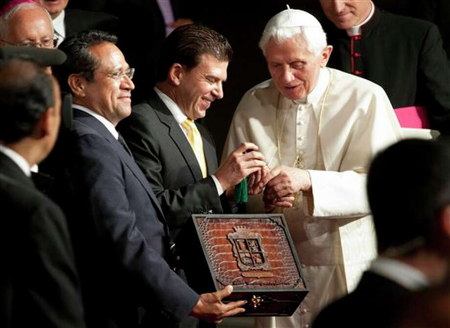 Pope Benedict XVI receives the symbolic key of the city from Leon Mayor Ricardo Sheffield, center, and Guanajuato Gov. Juan Manuel Oliva, left, in Leon, Mexico, Saturday March 24, 2012. Benedict arrived in Mexico Friday afternoon, a decade after the late Pope John Paul II's last visit. The pontiff's weeklong trip to Mexico and then to Cuba on Monday is his first to both countries. (AP Photo/Eduardo Verdugo) Photo: Associated Press