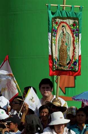 A man hold an images of the Virgin of Guadalupe as he waits for the arrival of Pope Benedict XVI to the symbolic key ceremony in Guanajuato, Mexico, Saturday March 24, 2012. At the entrance to the historic city, Benedict received the keys. The pope reserved his only public remarks Saturday for a gathering of about 4,000 children and their parents massed in Guanajuato's Plaza de la Paz or Peace Plaza.  Photo: Associated Press