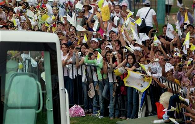 Faithful wave to Pope Benedict XVI as he passes by in his popemobile on his way to the Plaza de la Paz or Peace Plaza, in Guanajuato, Mexico, Saturday March 24, 2012. Benedict arrived in Mexico Friday afternoon, a decade after the late Pope John Paul II's last visit. The pontiff's weeklong trip to Mexico and then to Cuba on Monday is his first to both countries.  Photo: Associated Press
