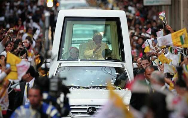 Pope Benedict XVI waves to faithful from his popemobile as he makes his way to Plaza de la Paz or Peace Plaza in Guanajuato, Mexico, Saturday, March 24, 2012. At the entrance to Guanajuato, Benedict received the keys to the city. The pope reserved his only public remarks Saturday for a gathering of about 4,000 children and their parents massed in the plaza.  Photo: Associated Press