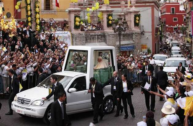 Pope Benedict XVI waves to faithful from his popemobile as he arrives in Guanajuato, Mexico, Saturday March 24, 2012. At the entrance to Guanajuato, Benedict received the keys to the city. The pope reserved his only public remarks Saturday for a gathering of about 4,000 children and their parents massed in the Plaza de Paz or Peace Plaza.  Photo: Associated Press