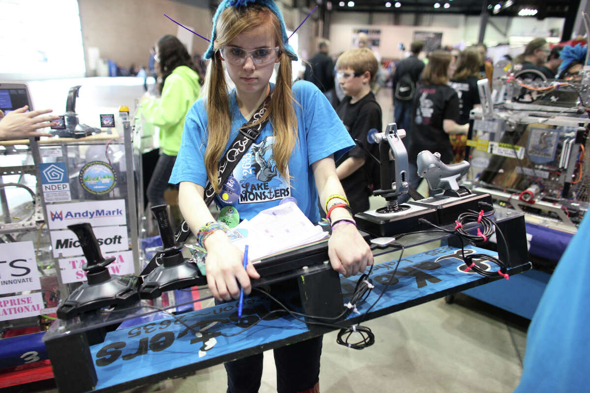 A student carries a control panel during the FIRST Robotics regional