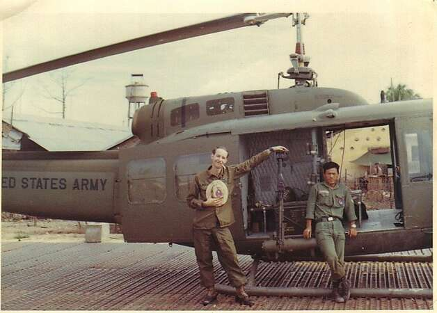 Wayne Terry, left, of San Francisco, with an unidentified South Vietnamese army officer, in front of the Huey in which he served as crew chief/door gunner.  The picture was taken somewhere in the delta region south of Saigon, in the fall of 1969.  Terry is active in Huey Vets, which helped assemble the Vietnam War helicopter at the Oakland Museum of San Francisco. Photo is courtesy of Wayne Terry. Photo: Bernard Iribarren
