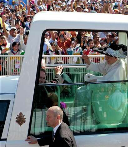 Pope Benedict XVI waves from the popemobile wearing a Mexican sombrero as he arrives to give a Mass in Bicentennial Park near Silao, Mexico, Sunday March 25, 2012.  Photo: Eduardo Verdugo, Associated Press / Copyright 2012 The Associated Press. All rights reserved. This material may not be published, broadcast, rewritten or redistributed.