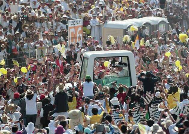 Pope Benedict XVI waves from the popemobile wearing a Mexican sombrero as he arrives to give a Mass in Bicentennial Park near Silao, Mexico, Sunday, March 25, 2012.  Photo: Gregorio Borgia, Associated Press / AP
