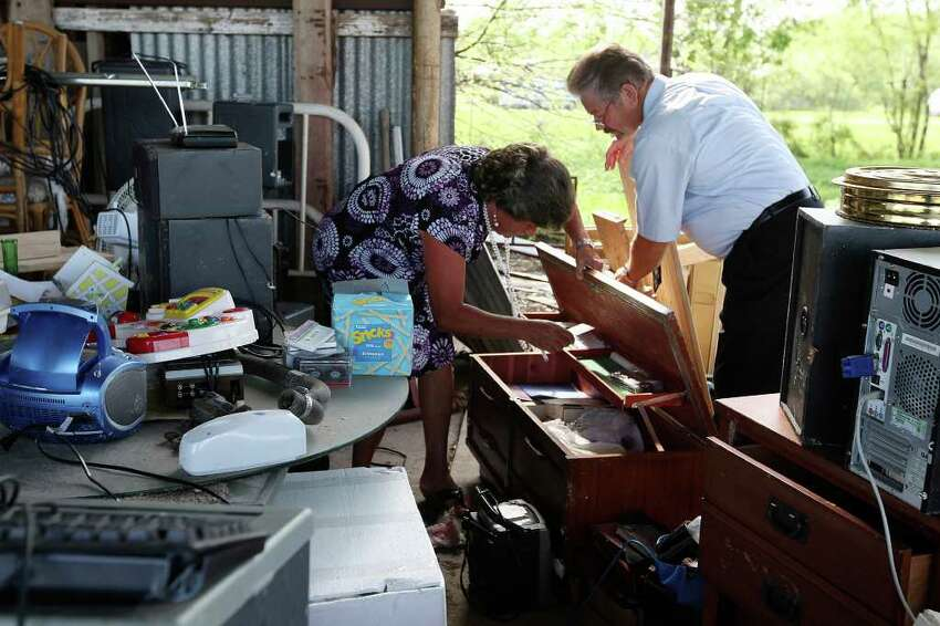 Faith Tabernacle Full Gospel Church Pastor Darrell Mellene (right), and his wife, Lou, look for items among salvaged belongings as they prepare to hold an outdoors Sunday Service, March 25, 2012. The church building, located just west of Devine, was destroyed by a tornado last week.
