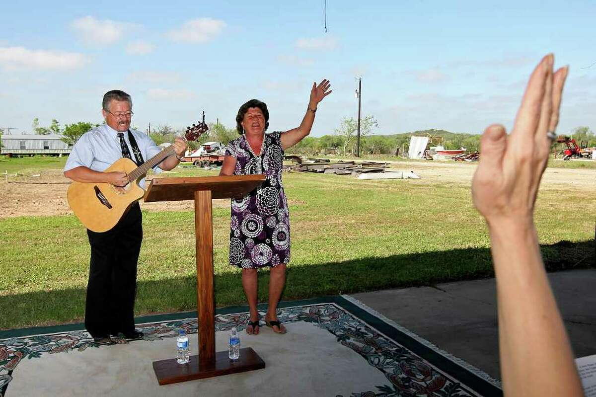 Faith Tabernacle Full Gospel Church pastor Darrell Mellene and his wife, Lou, hold a service in front of wreckage from their church near Devine and the bare patch of ground where the building stood before a tornado destroyed it last week.