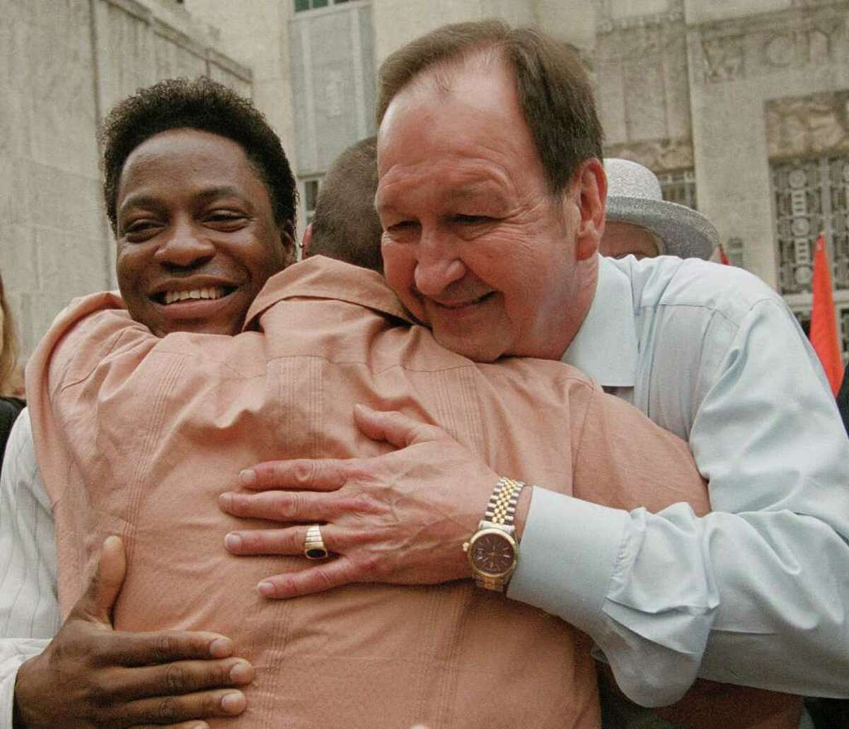 Tyron Garner, left, and John Geddes Lawrence, right, are hugged by a well wisher after a rally at Houston City Hall on June 26, 2003, held to celebrate the Supreme Court ruling striking down a Texas law that bans gay sex acts.