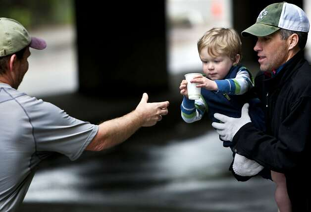 George Saunders, 2, with Coach Art, hands a cup of water to a marathon runner on Sunday at Broadway in Oakland. Marathon runners faced a 26 mile trek through Oakland on Sunday during the annual Oakland Running Festival. The race started at 7:30 am at Snow Park, and tread through areas such as Montclair, Moon Temple, and Lake Temescal. Photo: Kevin Johnson, The Chronicle