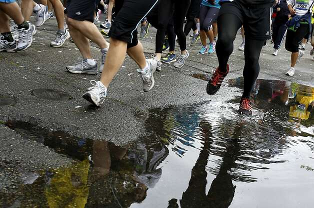Rain puddles got in the way of some runners of the half marathon as they made their way up 19th Street. The Oakland Running Festival avoided the rain at the start of the marathon Sunday March 25, 2012. Photo: Brant Ward, The Chronicle