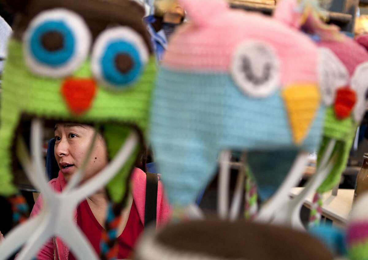 Jill Lou of Knitnut by JL greets customers at her booth during the Treasure Island Market indoor sale in San Francisco on Sunday. Lou hand-knits caps that reflect popular video-game and cartoon characters. Dozens of vendors crammed into the Administration Building at Treasure Island in San Francisco on Sunday to sell hand-crafted and unique goods during the final day of the Treasure Island Flea Market indoors season.